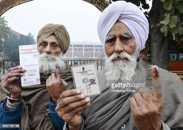 Two old man showing their inked fingers after coming out of polling booth on February 4 2017 in Amritsar India Punjab on Saturday voted in its first...