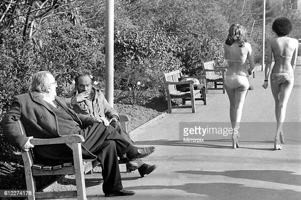 Two old men sitting on a park bench distracted by models in bikini walking past February 1975 7501132008