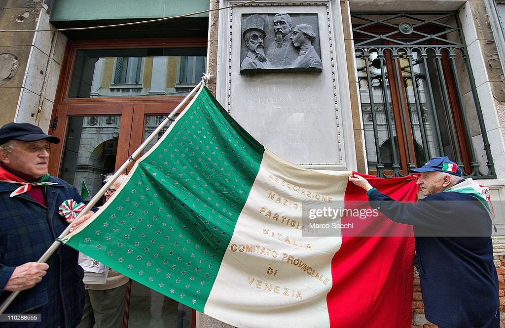 Two old partisans prepare their flag under a stone remembering martyrs of the Risorgimento on the day of the celebrations for the 150th anniversary of Italy's unification on March 17, 2011 in Venice, Italy. Events in various Italian cities will celebrate the 150th anniversary of Italy's unification until the end of the year. National Festivity begins on March 17.