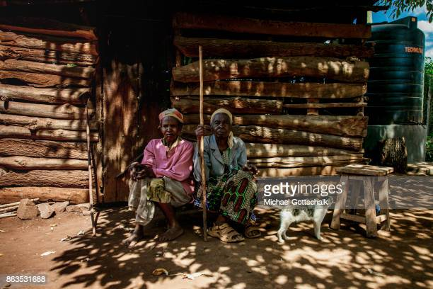 Two old women sit next to their houuse on farm on which plants grow with the support of the irrigation system of local farming cooperative Mitooini...