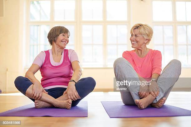 Two old women sitting on exercise mat at gym