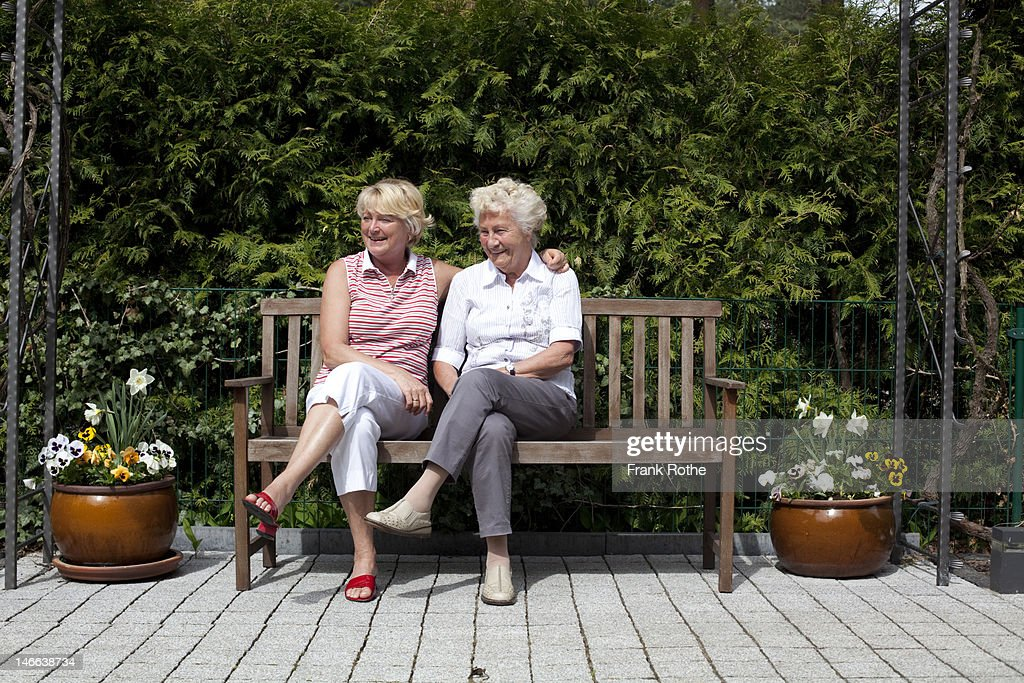two older women sit on a bench in a garden : Stock Photo