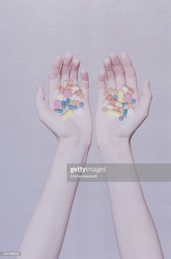Two open hands holding medicine