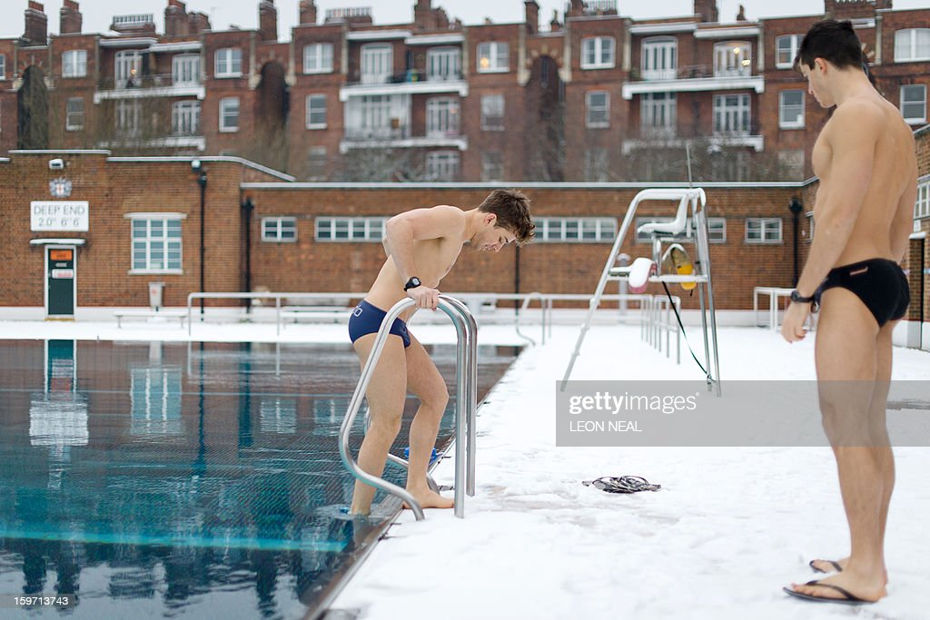 Two open-air swimming enthusiasts prepare to take to the icy waters at a lido in north London on January 19, 2013. While some people are savouring the cold conditions, snow that swept across Britain on January 18 continues to cause travel difficulties across the country. AFP PHOTO / LEON NEAL