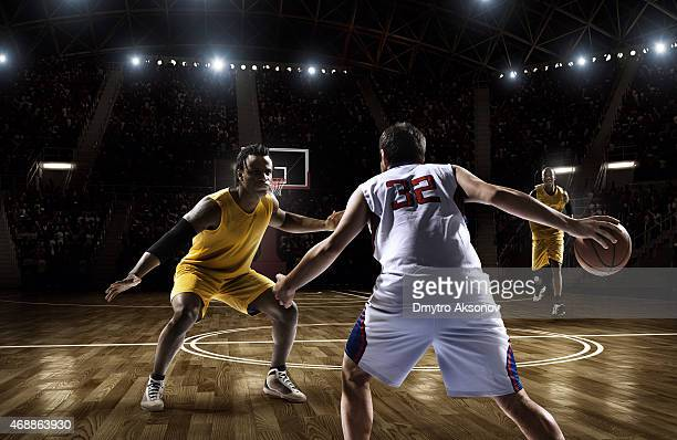 Two opposing basketball players facing each other