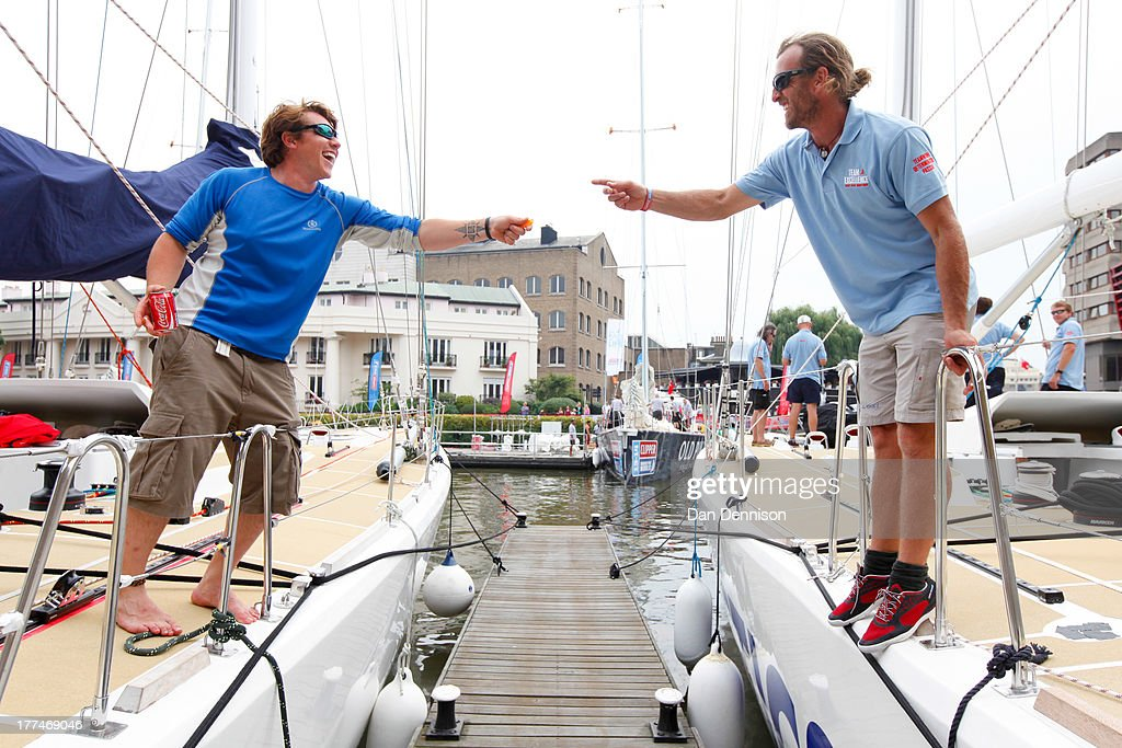 Two opposing crew members competing in The Clipper 2013-14 Round The World Yacht Race, share a light in St Katherine's Dock, east London on August 23, 2013. The 40,000 mile, 8-leg course begins on September 1 and will visit six continents, taking eleven months to complete.