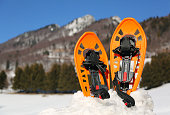 two orange snowshoes in mountains in winter with snow