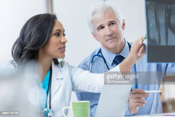 Dos médicos ortopédicos discuten radiografía del paciente