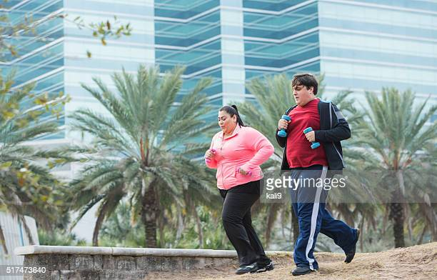 Two overweight people exercising, jogging with dumbbells