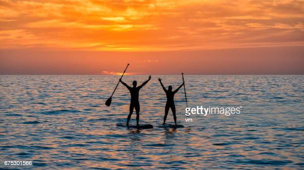 Two paddle boarders with raised arms at sunset