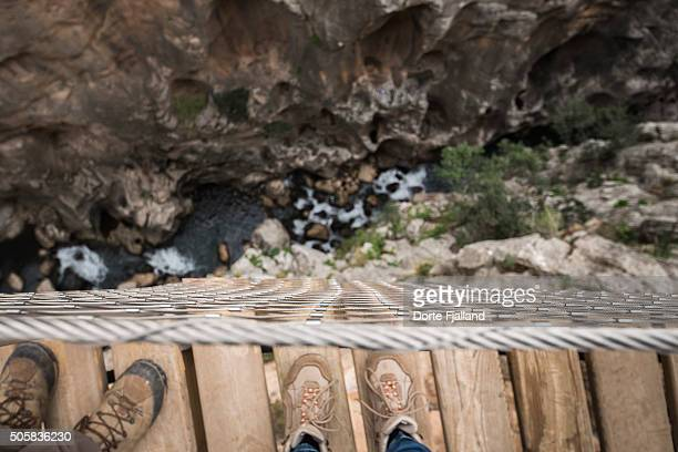 Two pairs of feet at the edge of a bridge