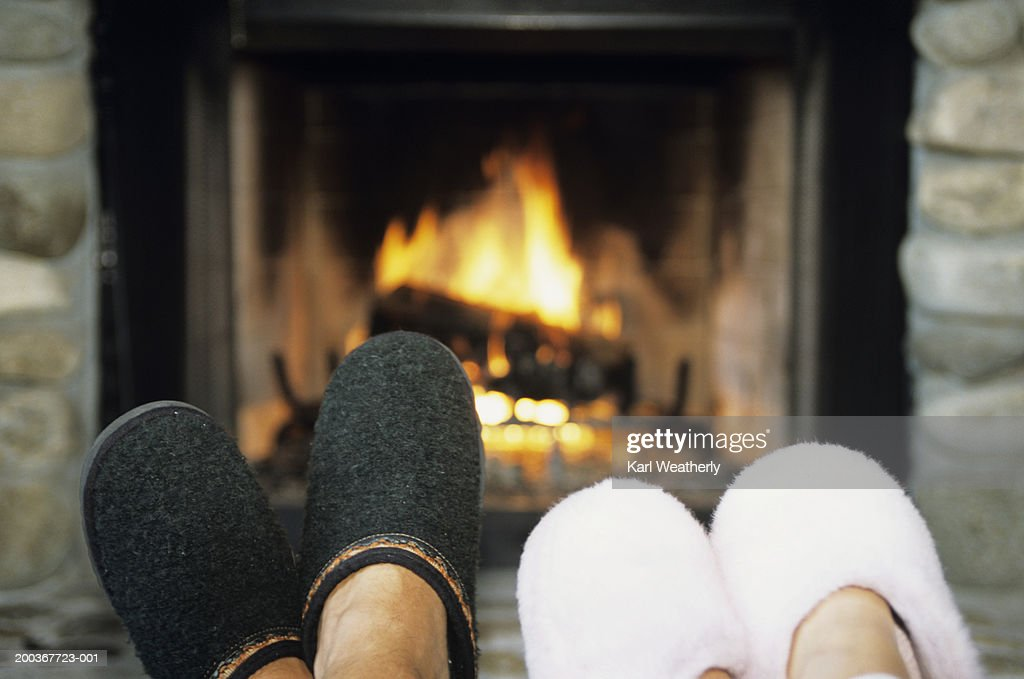 Two pairs of feet with slippers in front of fireplace, close-up, low section