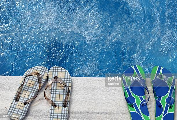 Two pairs of flip flops beside a swimming pool