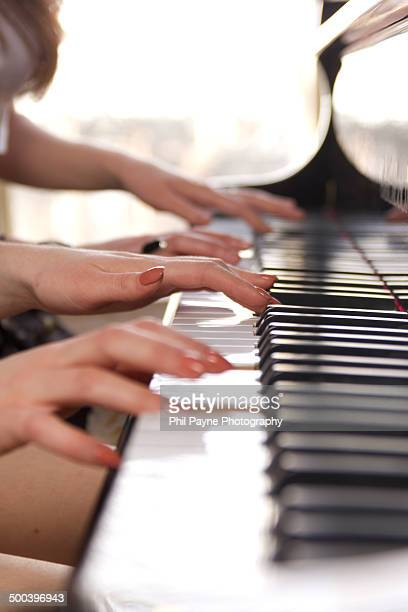 Two pairs of hands playing a duet