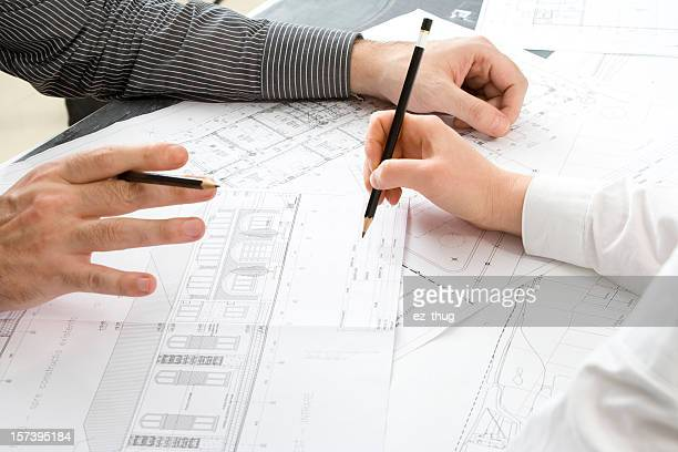 Two pairs of hands working on architectural drawings