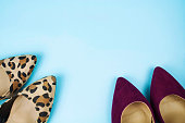 A pair of leopard print stilettos and another pair of burgundy stilettos on light blue background.