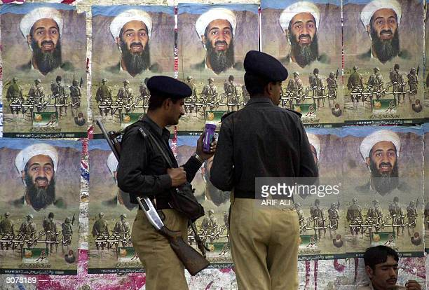 Two Pakistani policemen inspect a bottle of herbal medicine supposed to cure diabetes promoted by the use of posters of alQaeda's leader Osama...