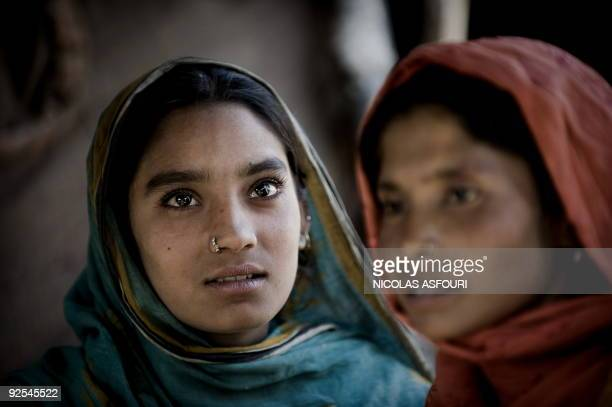 Two Pakistani women sit in the shade in a slum in Rawalpindi on the outskirts of capital Islamabad on October 25 2009 The insurgencyhit country is...
