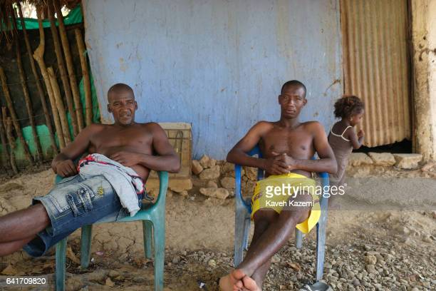 Two Palenquero men sit idly outside a building where a little girl is seen playing in the back on January 28 2017 in San Basilio de Palenque Colombia...