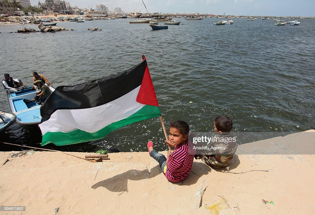 Two Palestinian children attend a protest, demanding lifting the blockade of Israel in Gaza City, Gaza on May 24, 2016.
