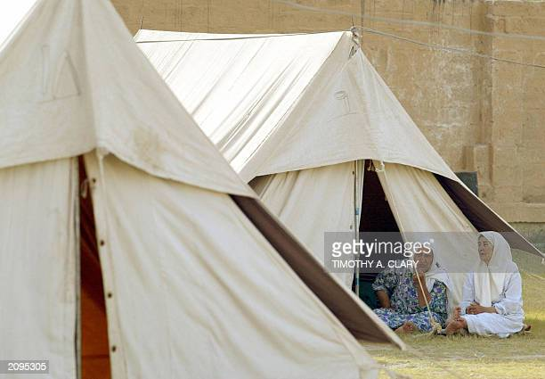 Two Palestinian sit outside their tent at a makeshift refugee camp formerly housing the Palestinan Sports Club in Baghdad 14 June 2003 About 1000...