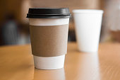 Two paper coffee cups on wooden table
