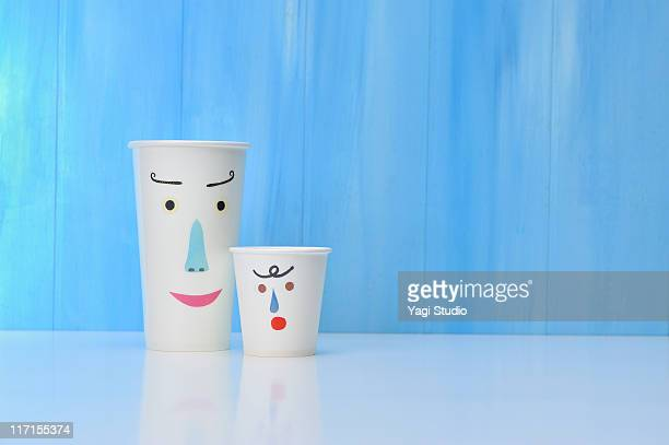 Two paper cups with the face