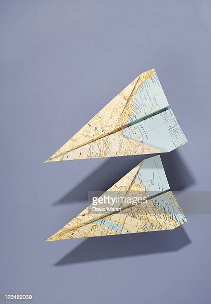 Two paper jets folded from maps.