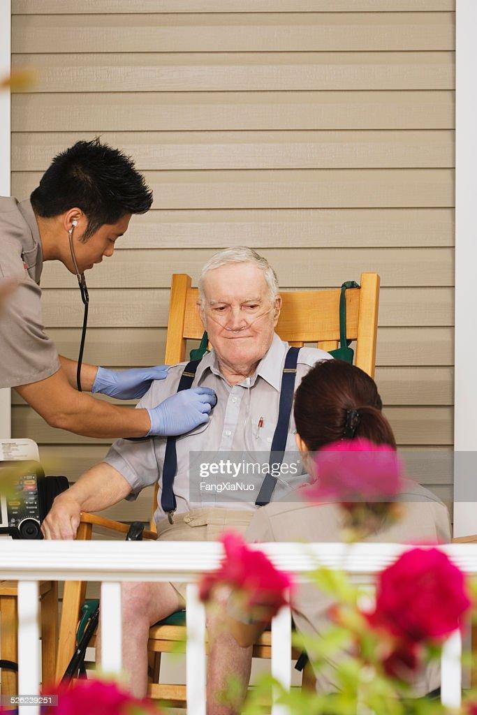 Two paramedics examining senior man on porch