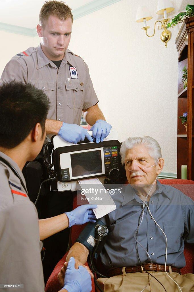 Two paramedics examining senior man with monitor
