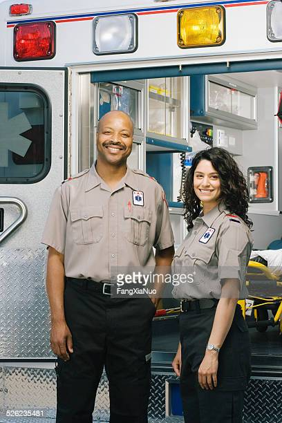 Two paramedics outside ambulance, portrait
