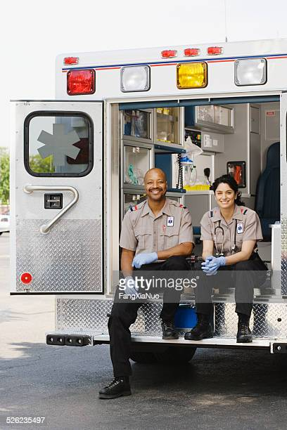 Two paramedics sitting in ambulance, portrait