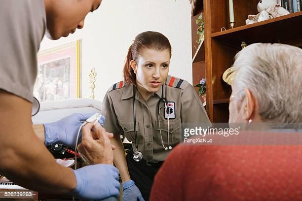 Two paramedics talking to senior man and examining his pulse