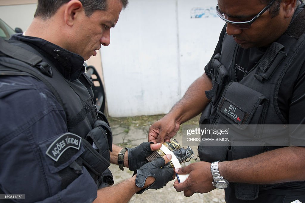 Two Paramilitary Police's elite unit BOPE members put tape around two grenades seized during an operation at Serrinha shantytown in Madureira, Rio de Janeiro, Brazil on February 6, 2013. AFP PHOTO/CHRISTOPHE SIMON