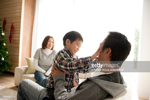 Two Parents and Son in Living Room at Christmas