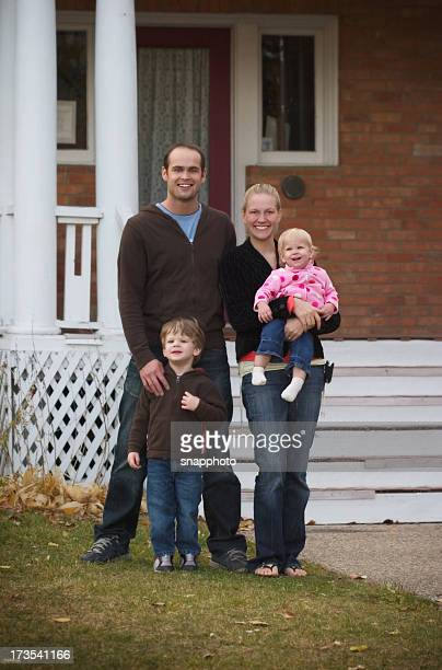 Two parents and two children on lawn in front of home