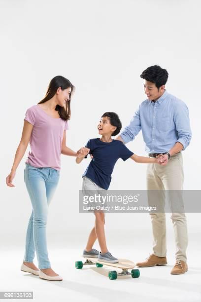 Two parents teaching son skateboarding