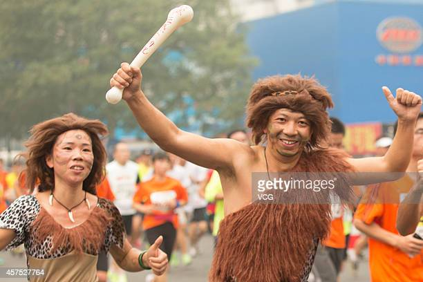 Two participants dressed as the figures in 'the Croods' run in the 2014 Beijing International Marathon in the captical of China on October 19 2014...