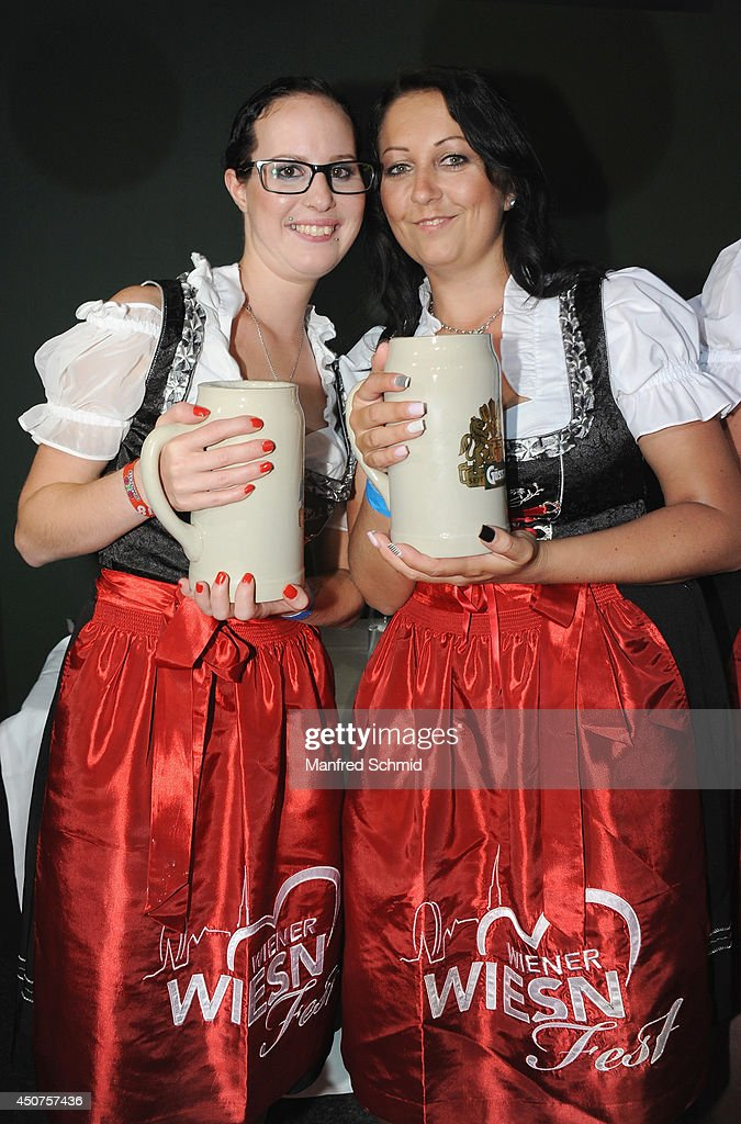 Two participants wearing traditional Austrian outfit Dirndl pose for a photograph during the beauty competition 'Miss Wiener Wiesn-Fest 2014' at Platzhirsch on on June 12, 2014 in Vienna, Austria.