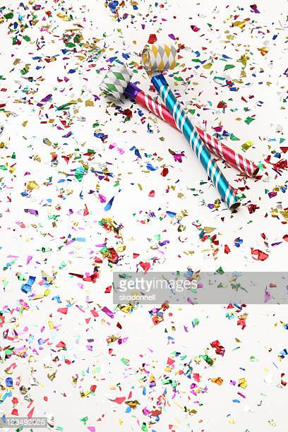 Two Party Horn Blowers Surrounded by a lot of Confetti