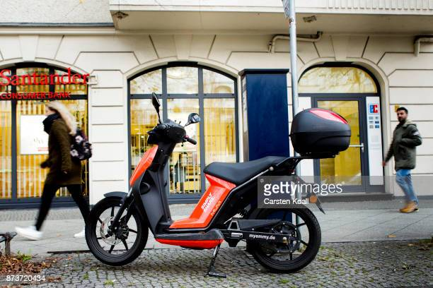 Two passersby pass by a scooter of the sharing agency Emmyon November 13 2017 in Berlin Germany A number of companies have plunged into the market...