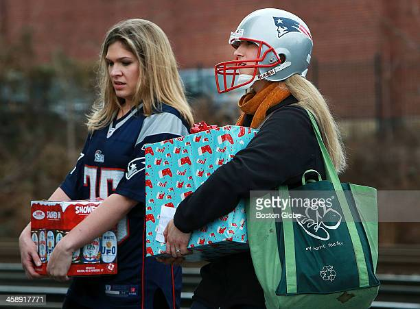 Two Patriots fans outside the stadium are prepared with libations a package wrapped in Christmas paper and aPatriots helmet The New England Patriots...