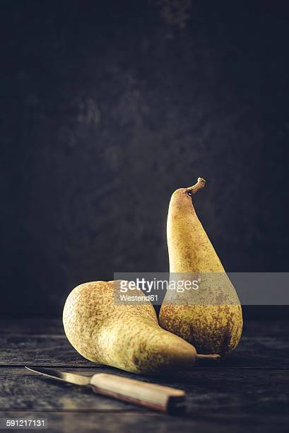 Two pears and a kitchen knife in front of dark background