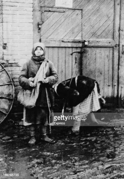Two peasant women collecting fallen grain on a collective farm near Belgorod during the manmade Holodomor famine in the Ukraine former Soviet Union...