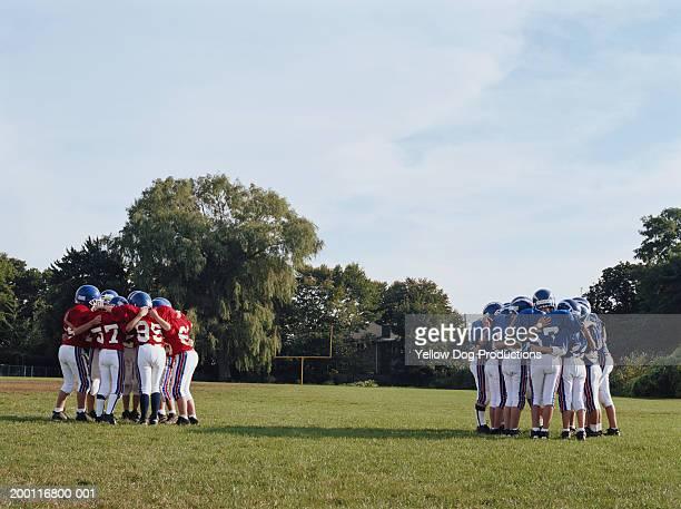 Two pee wee football teams in huddle on field