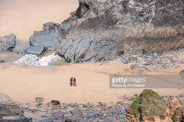 Two people admire the rocks at Bedruthan steps