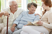 Two elder people are looking at smiling nurse who reads book in common room