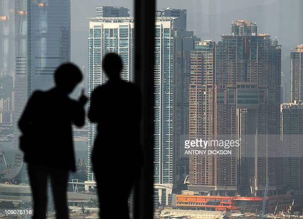 Two people are silhouetted as they look towards residential properties on the Kowloon peninsula from Hong Kong island on October 27 2010 Hong Kong's...