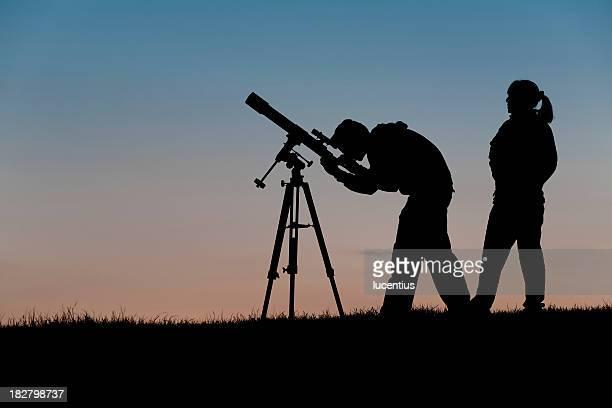 Duas pessoas a uma observação à noite clube Astronómico