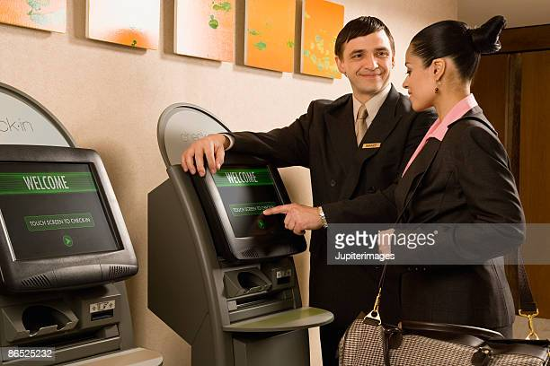 Two people at touch screen kiosk